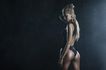 Beautiful shapely athletic big breasted  blonde girl with wet oiled body wearing black translucent sexy bodysuit posing with her back in scenic smoke under falling water drops on black