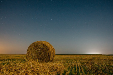 Night field with a haystack under a beautiful night sky