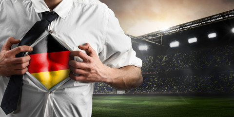 Germany soccer or football supporter showing flag under his business shirt on stadium.