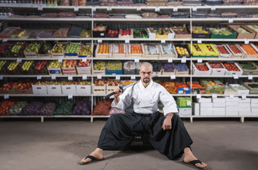 A man against the background with racks with fruits and vegetables dressed in Japanese kimono and hakama holding katana. Fruitarianism concept