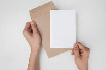 Hands holding brown envelope with a empty paper on white background