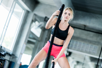 attractive caucasian woman workout with rope morning fitness at gym
