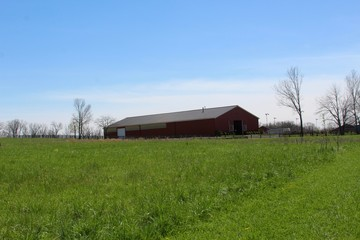 The old wood barn in the green field of the countryside.