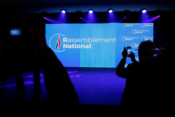 Members of the media picture the new logo of the National Rally (Rassemblement National) party after French politician Marine Le Pen (not pictured) delivered a speech to announce the new name of the far-right National Front political party during a nationa