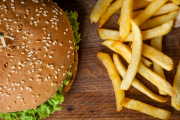 American burger and French fries on a wooden board. Photo from the top