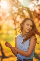 Joyful funny teen girl on a walk in the flower garden.