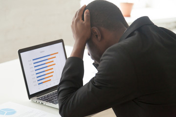 Disappointed stressed African American manager holding head in hands looking at laptop screen, observing falling rates online, witnessing business collapse, company failure. Bankruptcy, loss concept