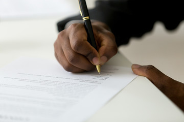 Close up of African American worker signing job contract, person being employed at new position, male client putting signature at document in office. Recruiting, promotion, legal documentation concept