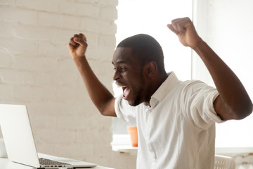 Excited amazed black worker throwing hands up, screaming celebrating online win, earning money, reaching goal, getting loan. Happy African American feeling euphoric after company business breakthrough
