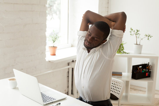 Tired male African American worker stretching in office chair, exhausted after long hours hardworking, person relieving muscle tension by doing office gymnastics. Concept of sedentary work, exercising