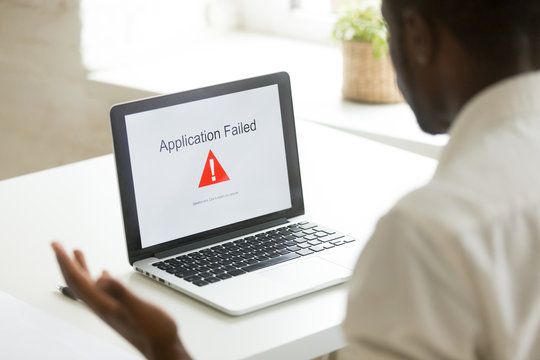 Frustrated unhappy worker getting application fail notice at laptop screen, malware program causing mistake operation problem leading to information leakage, data loss. Online virus, app crash concept
