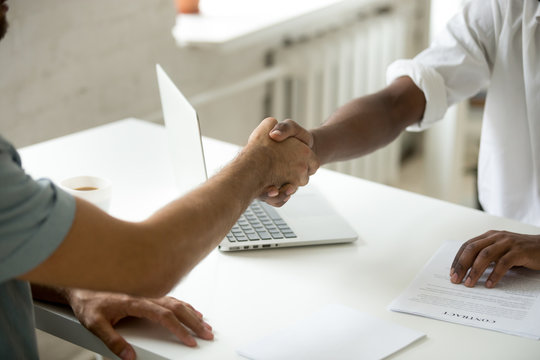 Close up of African American employer greeting caucasian job applicant with handshake, welcoming at potential workplace. Employee shaking hand of future boss making good first impression, closing deal