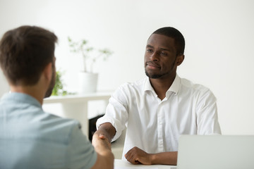 Satisfied casual African American employer shaking hand of Caucasian job applicant, congratulating with closing work contract, successful hiring, greeting at new position. Employment concept