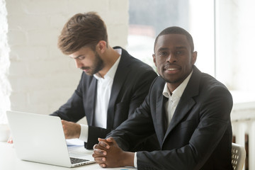 Smiling African American businessman in formal wear looking at camera during company business meeting with Caucasian colleague busy analyzing financial report. Concept of work diversity, cooperation