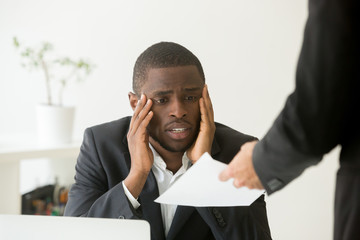 Frustrated upset African American worker getting dismissal notice, looking sad and in low spirits being fired from work and receiving termination letter. Concept of racial discrimination