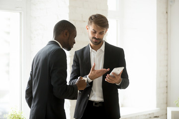 Caucasian businessman showing something on tablet to black male colleague drinking coffee. Partners discussing online marketing strategy, talking about web content. Partnership, technology concept