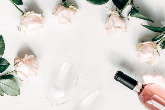 White roses, wine and glasses for wine a on light wood table. Flat lay, top view, copy space