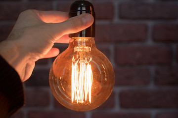 Decorative antique edison style light tungsten bulbs against brick wall background