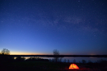 Night landscape with starry sky, Milky Way, lake in the background, and red illuminated tent in the foreground.