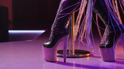 Sexy woman in high boots on platform and heel with rhinestones. Fringe skirt with pendants made of shiny stones. striptease dancer moving on stage in strip night club,