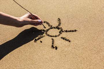 A female hand draws the sun on the sand