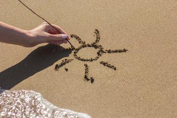Female hand draws the sun on the sand near the sea