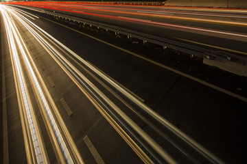 Night scene of motion blurred light tracks glowing to the darkness of highway traffic to the city just after sunset. Creative long time exposure diagonal composed photography.