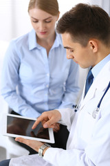 Male doctor using touchpad or tablet pc while consulting female patient in hospital office. Medicine and healthcare concept