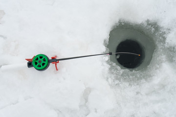 Fishing rod for winter fishing is on the ice. Wait for fish biting on winter fishing.