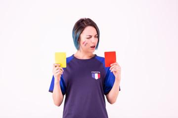 Portrait d'une jeune supportrice de l'équipe de France de football face à un carton jaune et rouge