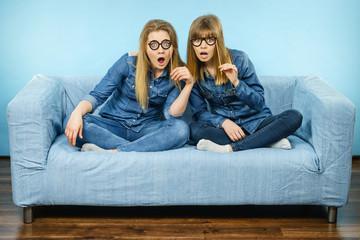 Two shocked women holding fake eyeglasses on stick