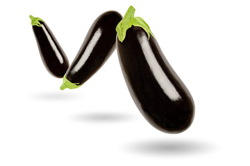 Three eggplants in a row floating in the air, on white background. Solanum melongena, also called aubergine or brinjal. Nightshade. Elongated oval shaped black skinned fruit. Macro food photo closeup.