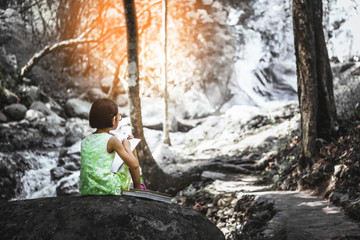 A little girl is sitting on stone and holding pencil whit paper will drowing waterfal in the forest