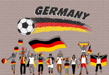 German football fans cheering with Germany flag colors in front of soccer ball graffiti