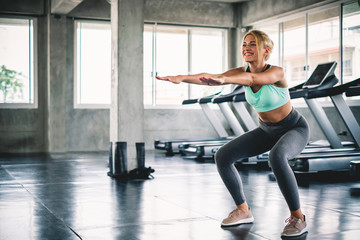 Woman body warm up by stretching arms and squat before workout and yoga at sport gym