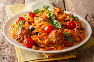 Delicious dinner: meat balls with pasta spaghetti, eggplant and tomatoes close-up on a plate. horizontal