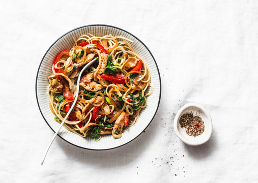 Teriyaki chicken, bell peppers, onions, spinach and rice noodles stir fry on white background, top view. Asian style healthy food