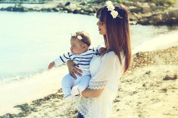 Jeune maman et son bébé portant une couronne de fleurs au bord de mer