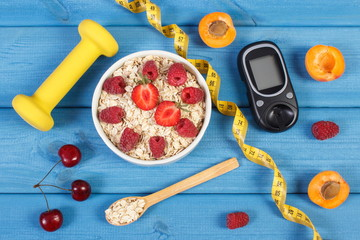 Glucose meter for measuring sugar level, oatmeal with fruits and dumbbells