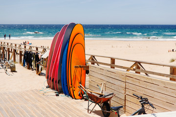 A wooden walkway to the ocean.Surfboards on a blue background. Background for design.