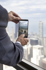 Businessman at Willis Tower taking a picture of Chicago skyline with his phone
