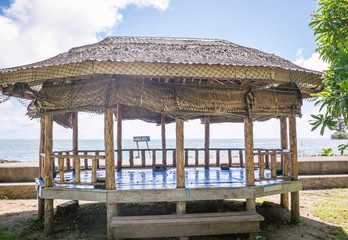 Open-sided beach hut or fale with woven palm leaf roof by waterfront near Pula Cave Pool, Upolu Island, Samoa, South Pacific