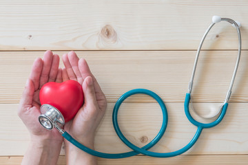 Healthcare medical insurance and World heart health day concept with red heart on woman's hands support