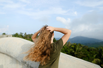 Young female person looking at mountains and wearing khaki dress. Concept of nature and relaxing.