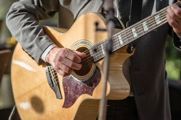Closeup of man's hands playing acoustic guitar. Musical concept.