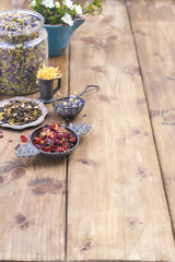 Assorted dried flowers and tea on a wooden background. Natural health. Aromatherapy. Free space for text. Copy space