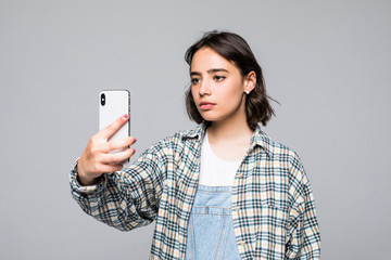 Smiling young girl making video call on smartphone over gray background