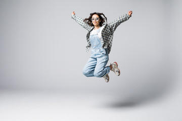 Full length portrait of a laughing woman jumping over gray background.