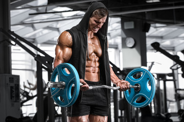 Muscular man working out in gym doing exercises with barbell for biceps, strong male naked torso abs
