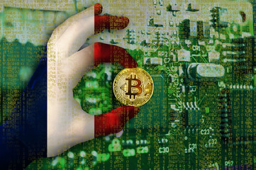 Bitcoin cryptocurrency France flag Binary code Golden Coin of Bitcoin in the French flag hand between two fingers shows OK sign on a chip background